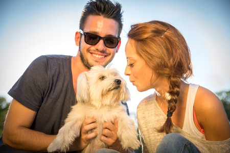Portrait of young happy couple with dog photo