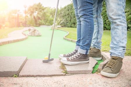 playing golf: Mini Golf -  Boyfriend teaching to his girlfriend how to putt
