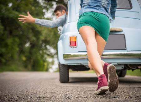Motor quebra down.Strong jovem mulher empurrando um carro do vintage ao homem encorajando her.Transportation, trabalho em equipe, conceito engraçado