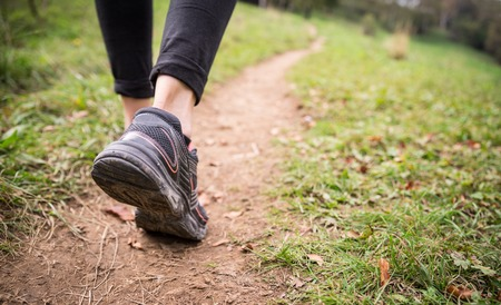 hiker: Woman walking on the path - Sportive girl running in a forest along a track Stock Photo