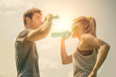 Couple drinking water after workout at sunset photo