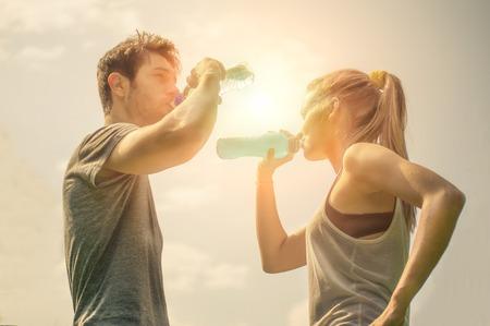 beber agua: Pareja de agua potable después del entrenamiento al atardecer