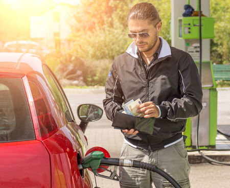 fueling: Young man filling car at gasoline tank while counting money Stock Photo