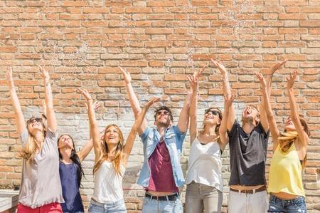 personas reunidas: Grupo de amigos que lanzan confeti en el aire - la felicidad, la venta, la amistad, el concepto de verano