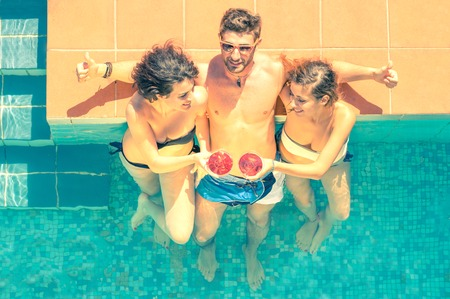 Friends having fun in a swimming pool Stock Photo