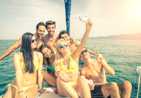 Group of friends on a boat taking a selfie Archivio Fotografico
