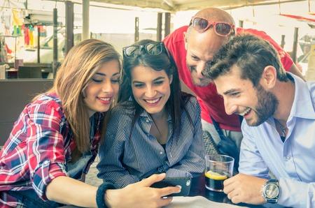 Groep vrienden bij het restaurant te kijken naar telefoon Stockfoto
