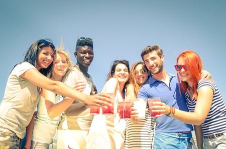 jovenes tomando alcohol: Grupo de amigos felices bebiendo c�cteles Foto de archivo