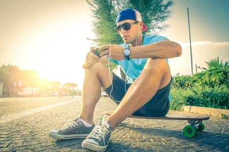Sportieve man bij zonsondergang muziek luisteren en kijken naar de telefoon