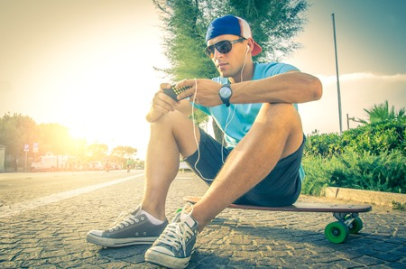 skater boy: Sportive man at sunset listening music and looking at phone Stock Photo
