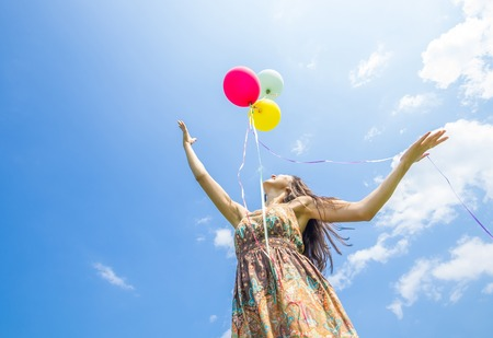 Attractive woman releasing balloons in the sky - Freedom,happiness,summer concept