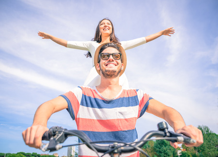 happy couple on  a bicycle. girl standing in the back with open arms photo
