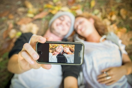 frienship: Selfie - Couple taking a self portrait while lying on meadow with yellow leaves