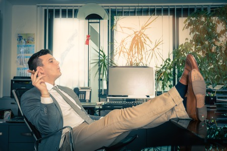 hard day at the office: Man smoking a cigar in his office - Business man enjoying his success Stock Photo