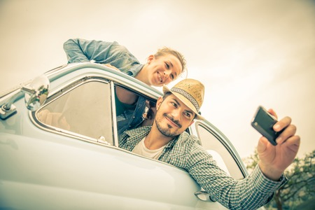 Happy couple on vintage car - Two friends photographing on a road trip - Concepts of couple,travel and fun