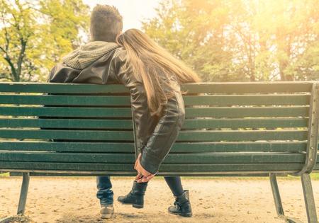 ロマンス: カップルのベンチ - 公園のベンチに座っていると手 - 秋の愛、連帯、関係の概念によって彼ら自身を保持している 2 人の恋人