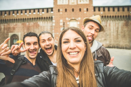 Group of friends taking a selfie - Tourists taking a photograph at Sforza Castle in Milan,Italy Фото со стока