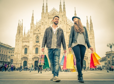 Echtpaar kopen tijdens een verkoop - Aantrekkelijke man en vrouw bedrijf boodschappentassen en met plezier - Herfst en winter stemming Stockfoto