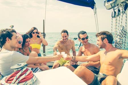 fiesta: Gente en un yate - Grupo de amigos tostado bebidas y que tiene partido en un barco de vela - Los turistas de vacaciones Foto de archivo