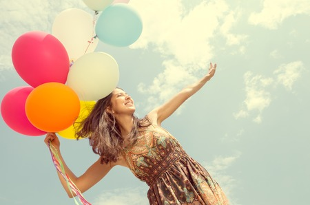 Portrait of young pretty woman holding balloons - Attractive model posing in front of camera outdoors - Vintage look
