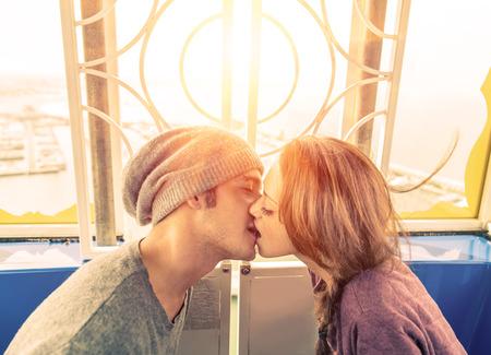 parejas jovenes: amor beso en una rueda panorámica