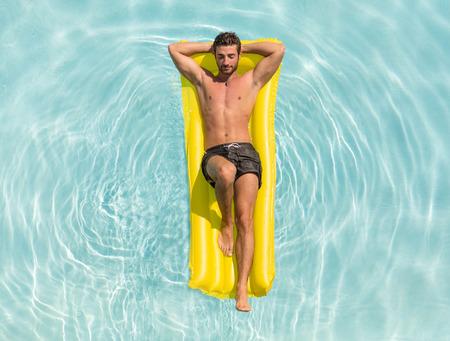 traje de bano: hombre disfruta de la vida en una cama de aire en la piscina