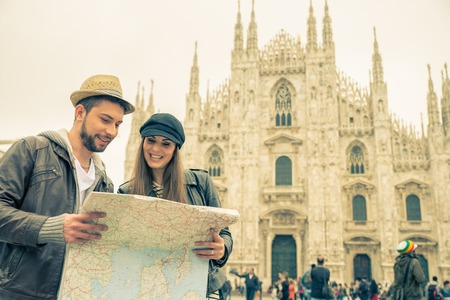 Happy tourists sightseeing city with map - Couple travelling in Italy Фото со стока