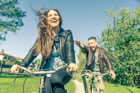 Couple riding on bicycles  and having fun - Tourists driving around the city - Two friends riding on bikes in the countryside
