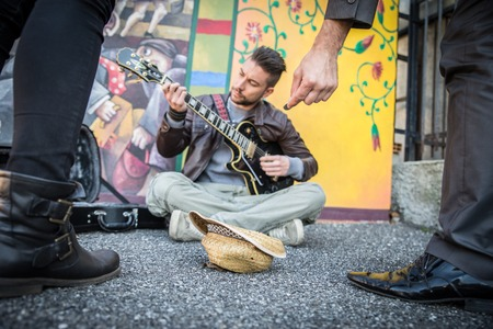 young musician: Street artist peforming om the streets - People listening man playing guitar and giving charity