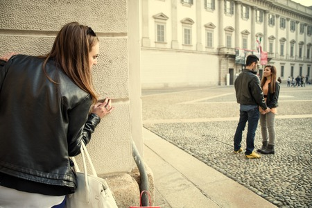 affairs: Stalking - Ex girlfriend spying her ex boyfriend with another woman - stalking,infidelity and jelousy concepts Stock Photo