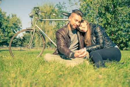 head on shoulder: Couple sitting on grass after a romantic tour with bicycle - Lovers looking at phone while relaxing in a park