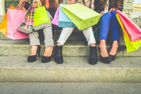 retail: Women with high heels and shopping bags - Three girls sitting on stairs and chatting after buying presents