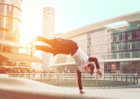 bailarin hombre: muchacho joven que hace parkour en un centro de negocios