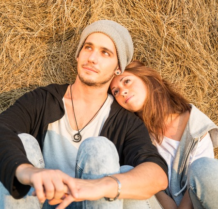 couples outdoors: Young couple sitting on a bale of hay