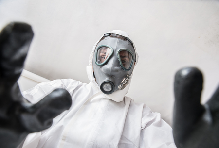 infective: Medical health care worker helping infected person in quarantine zone Stock Photo