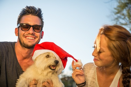 friendship day: Portrait of young happy couple and dog with christmas hat Stock Photo