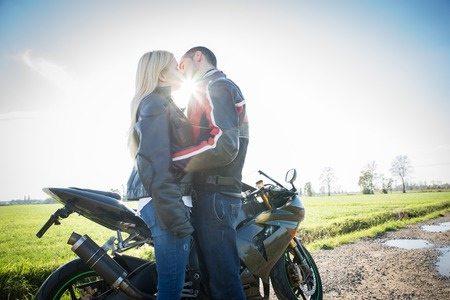 man arm: Couple of lovers kissing with motorbike in the background - Two bikers stop in the countryside