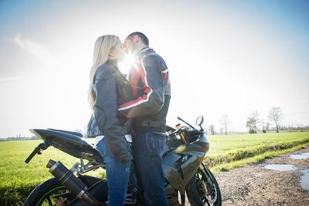motorrad frau: Liebespaar küssen mit dem Motorrad in den Hintergrund - Zwei Radfahrer zu stoppen auf dem Land