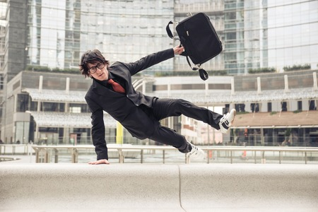 speedy: Business man with suitcase jumping over urban obstacles - Man with elegant suit running at work because in late - Concepts of business,overcoming problems,competition and urban urban life