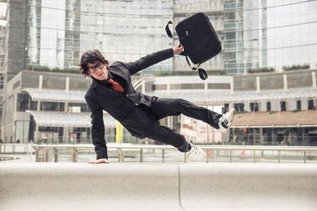 obstaculo: Hombre de negocios con la maleta de saltar por encima de obstáculos urbanos - Hombre con traje elegante corriendo en el trabajo debido a finales - Conceptos de negocio, la superación de problemas, la competencia y la vida urbana urbana