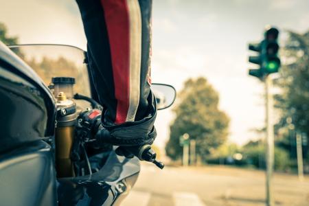 motociclista: Motorista en la carretera - Racing moto se detiene en los semáforos