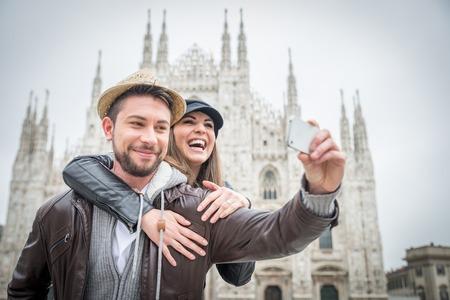 travel: 快樂的遊客以自畫像與手機在Duomo大教堂,米蘭面前 - 在意大利旅行的夫婦 版權商用圖片