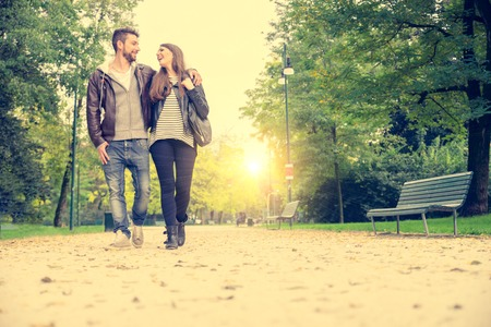 Couple walking hand in hand in a park - Romantic date outdoors Stock Photo