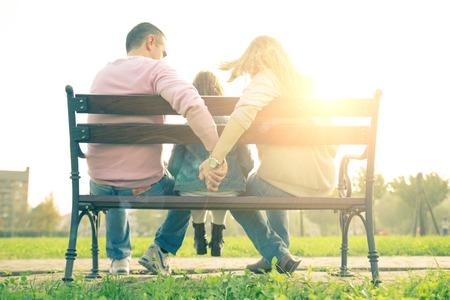 papa y mama: Familia que se sienta en un banco - Mamá y papá sosteniendo las manos con su hija sentada en el medio Foto de archivo