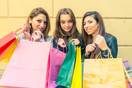 Women with shopping bags - Portrait of three pretty girls posing in front of camera photo