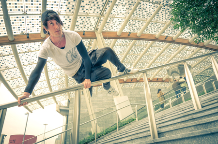 fleeing: Parkour athlete jumping over a handrail - Free runner performing tricks in a urban settlement - Parkour,free running,yoth,sport and lifestyle concept