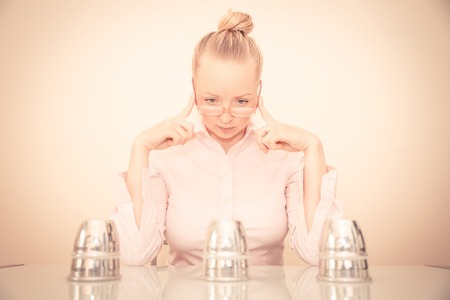 uncertainty: Undecided woman trying to find the ball under the cups - The gambling game of cups and ball - Concepts about business,uncertainty and making decisions Stock Photo