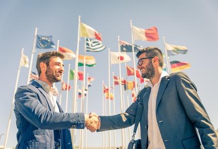 Business mannen handshake- Twee zakenlui lopen en praten buitenshuis Stockfoto