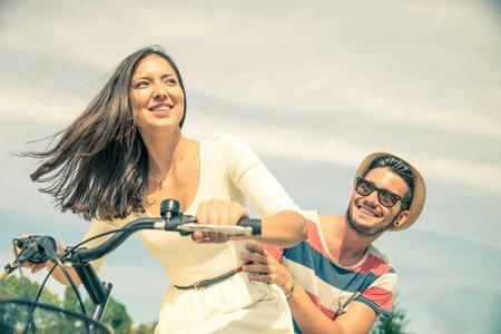amantes: Pareja feliz andar en bicicleta en la ciudad - Mujer bonita joven conducci�n de bicicleta y el hombre juguet�n sentado detr�s - Retrato de dos amantes al aire libre