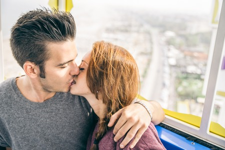 seducing: Couple enjoying a ride on a panoramic wheel - Lovers kissing and aerial view in background Stock Photo